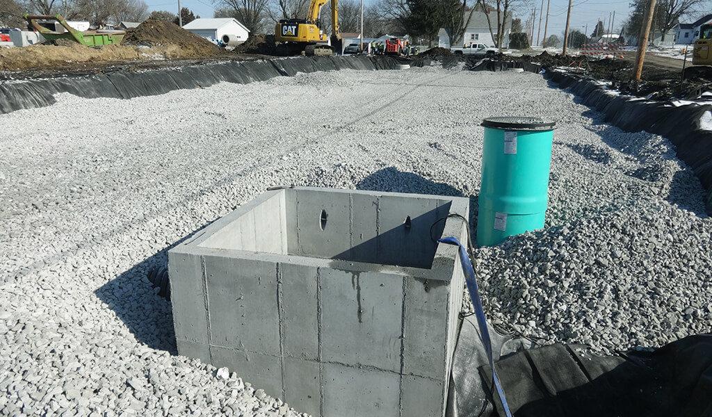 concrete detention basin along gravel roadway