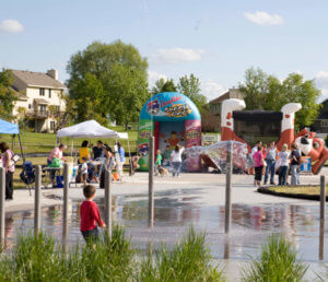 party at splash pad with large inflatables in the background