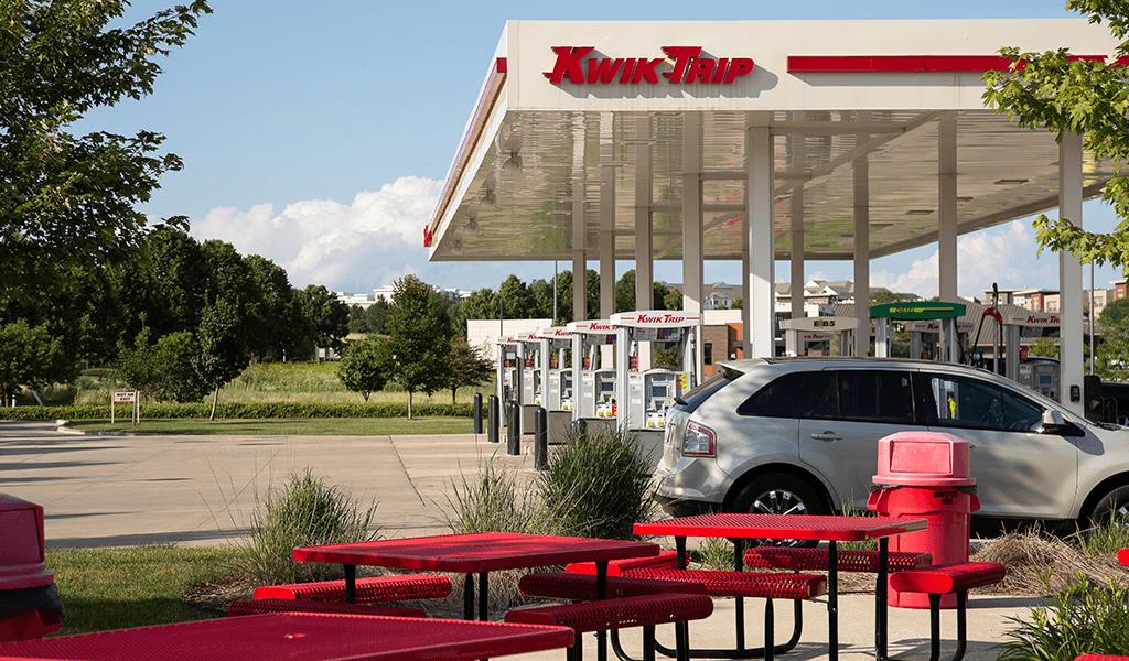 view of red tables and kwik trip gas pumps