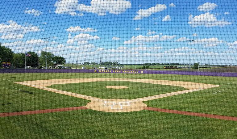 baseballfield through netting on a blue sky day