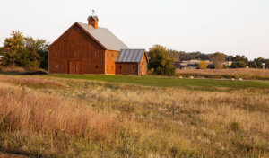 Large wood barn in grassy area