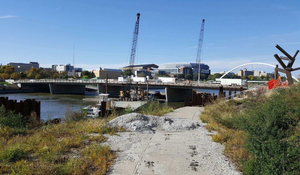 two large cranes working on bridge over river