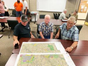 three elderly men look at a map