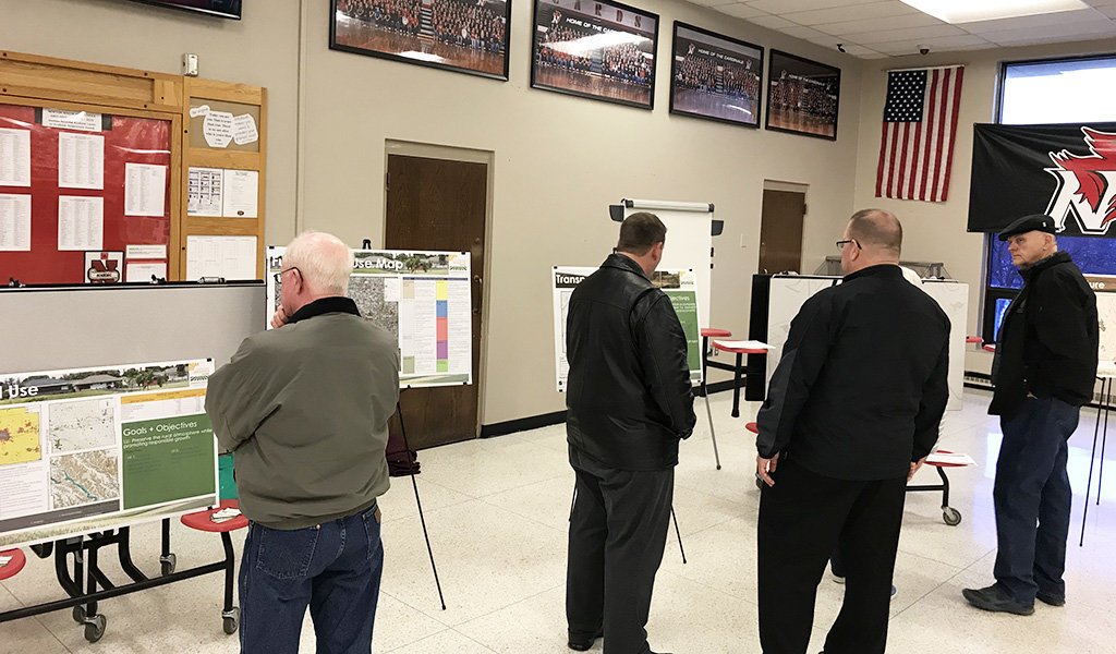a group of men looking at poster presentations
