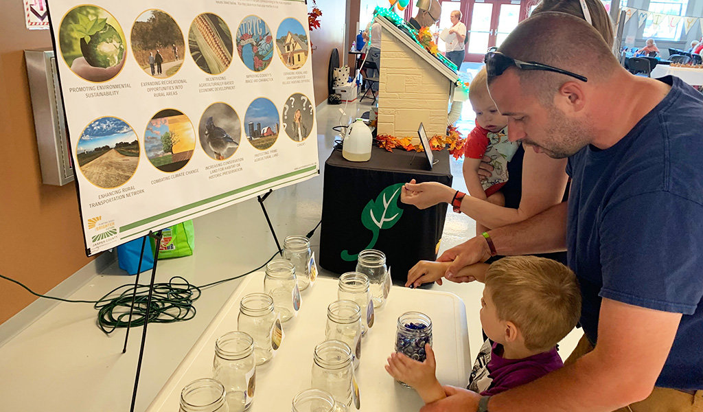 dad and son look at poster presentation and participate in jar activity