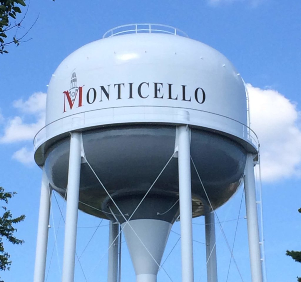 Freshly painted above ground water tower displaying the CIty of Monticello, Iowa logo.