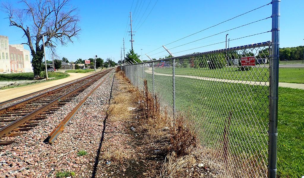 Railroad safety fence alongside a trail.