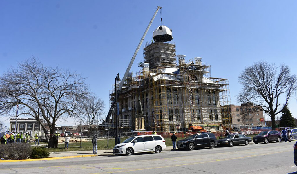 crane placing dome top back on courthouse building