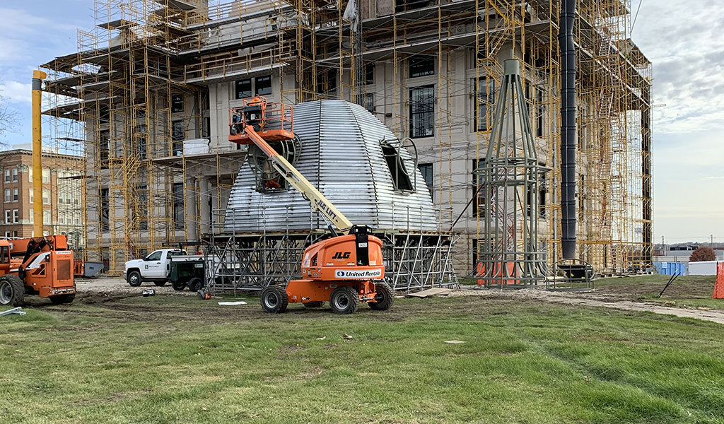 crews work on dome top while it's ground level