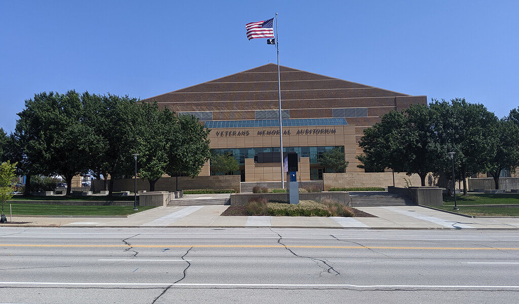 front of large auditorium with American flag flying