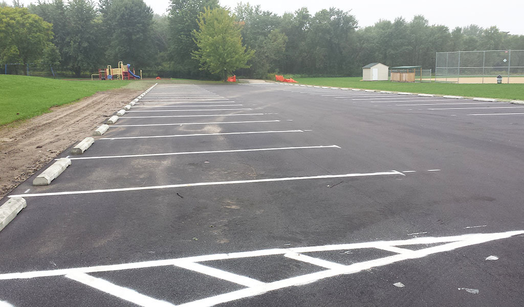 empty new parking lot next to a baseball field within Troy Park in Robins, IA