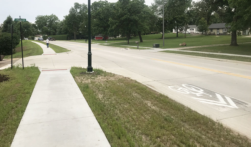 reconstructed street with shared bike lanes lined by ADA compliant sidewalks