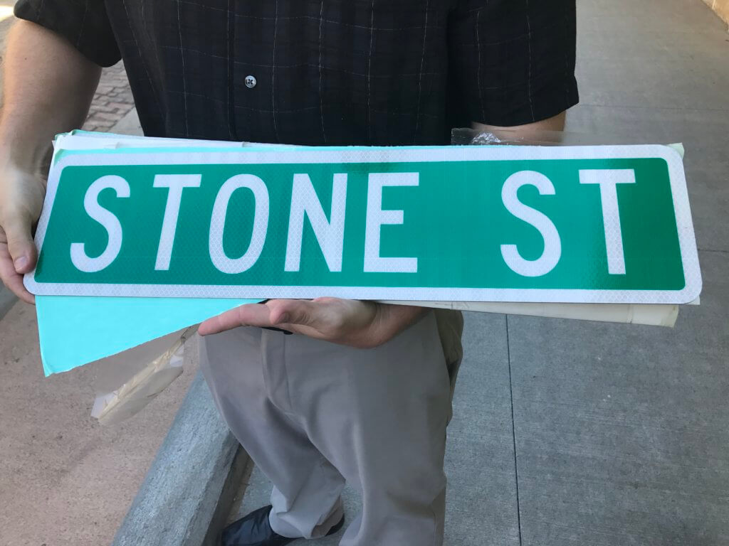 Close up of an unmounted street sign being held in the palm of a man.