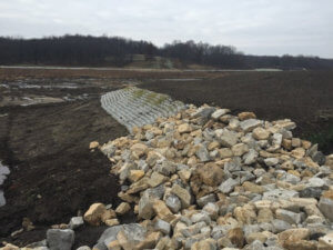 Riprap armoring and Flexamat concrete block mats provide stabilization along the reshaped shoreline.