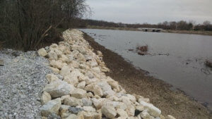 Large stones are used for shoreline stabilization around the fish rearing pond.