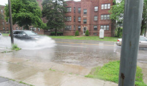 car sprays water while driving through a large puddle