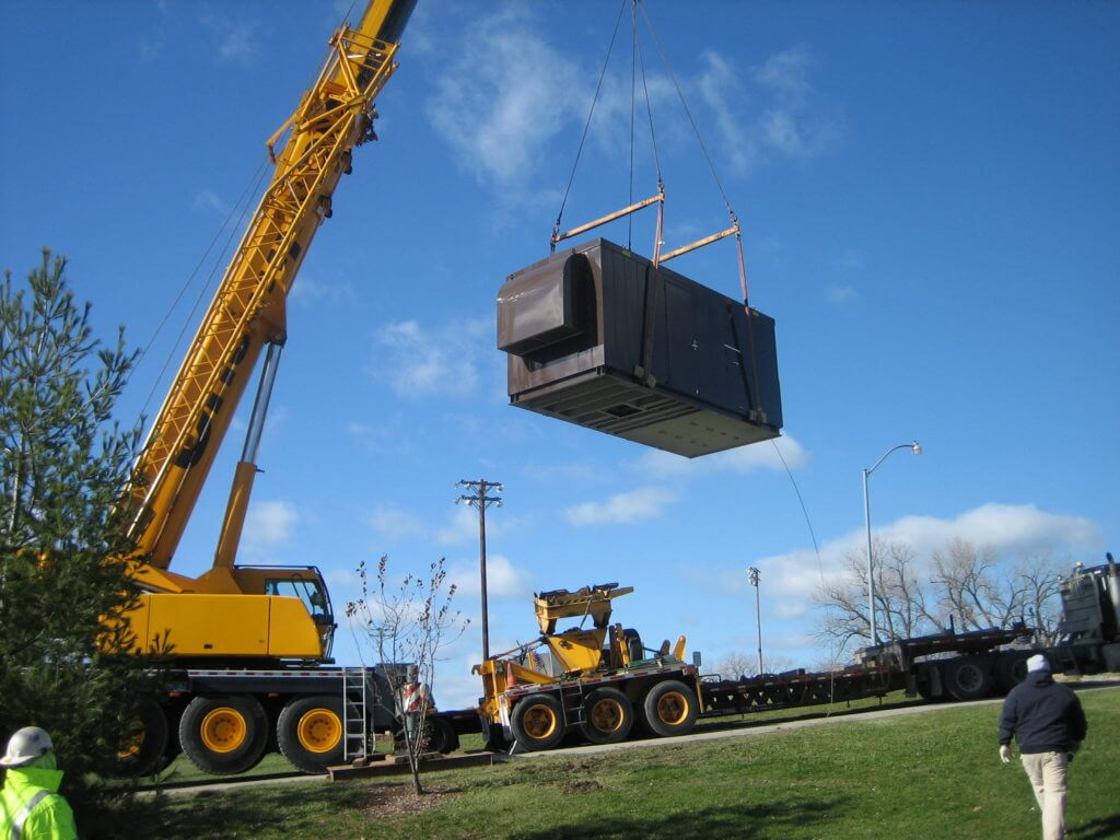 emergency generator being lowered into position by a crane at doanes park in pleasant hill iowa