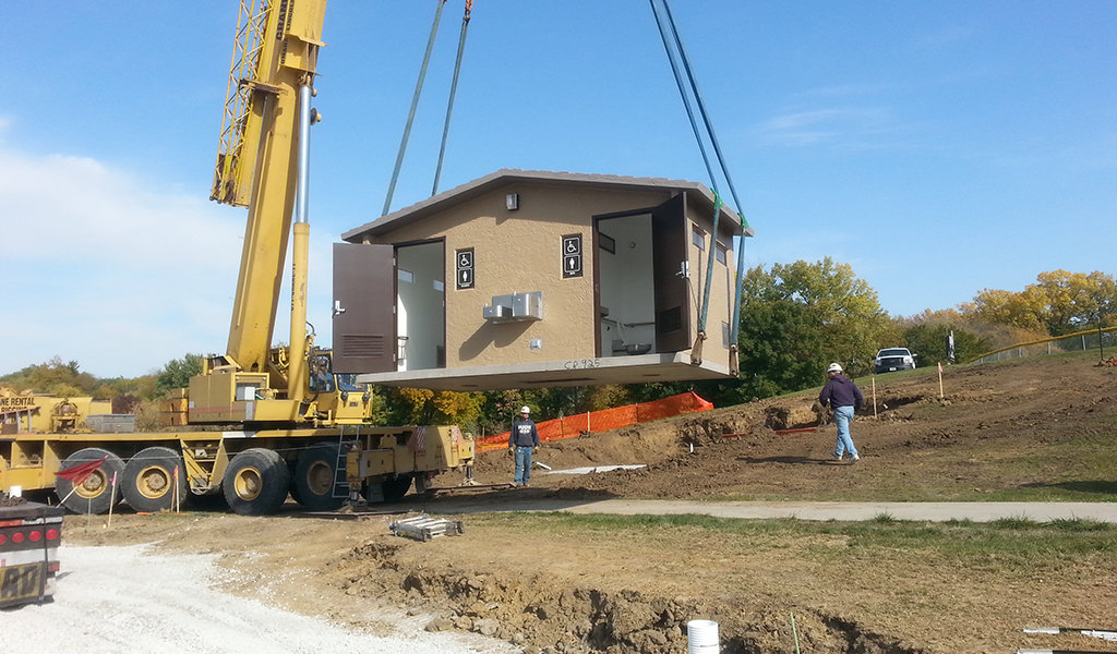 restroom facility being lowered into position by a crane at doanes park in pleasant hill iowa