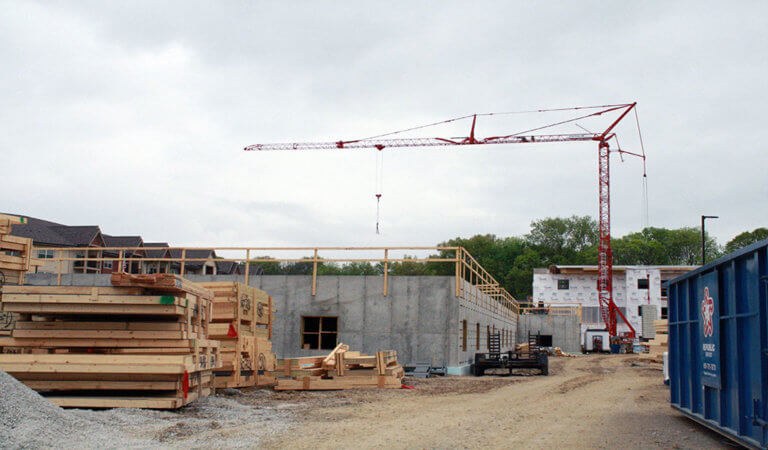 Large red crane over construction site and new building