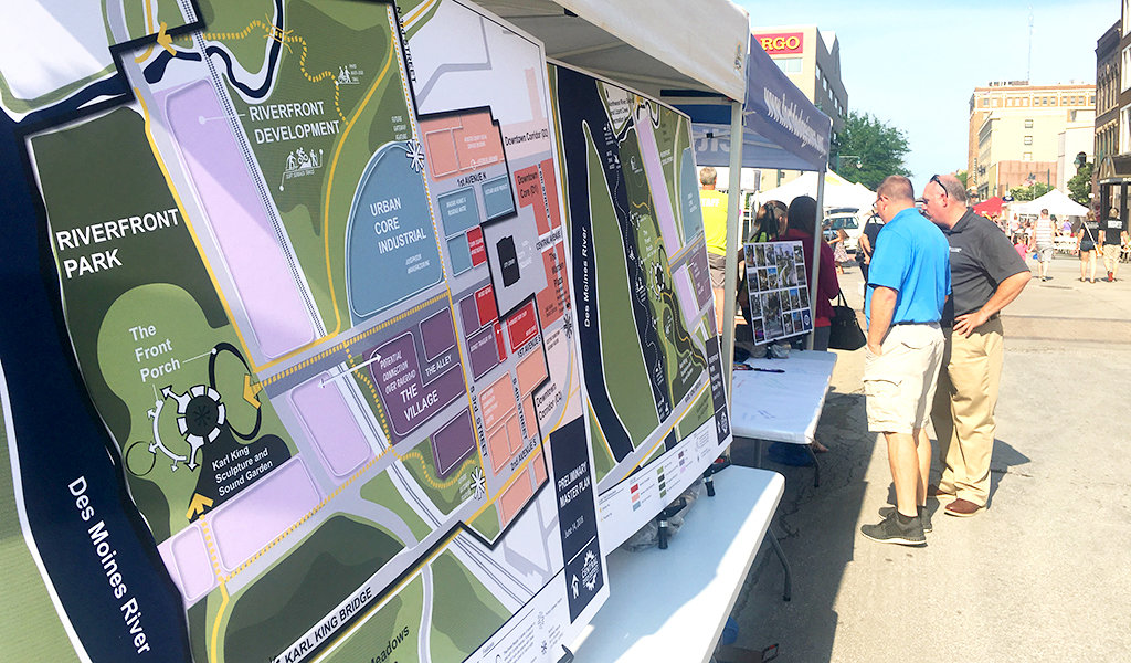two men looking at a master plan display for the central river district community forum in fort dodge, IA