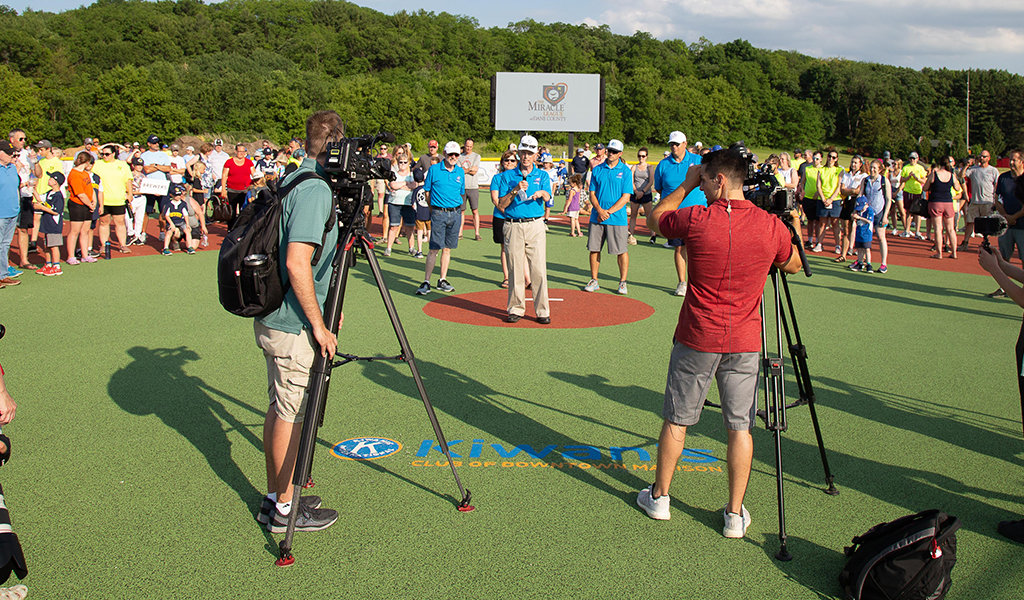 two film crews record a man on pitchers mound giving a speech