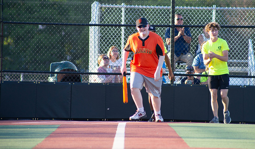 teen in orange jersey holds a bat after making a hit