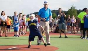 small child in head brace throws baseball