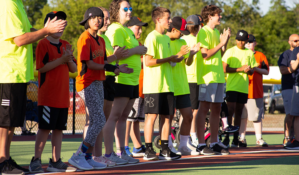 kids in neon shirts lined up on a turf field