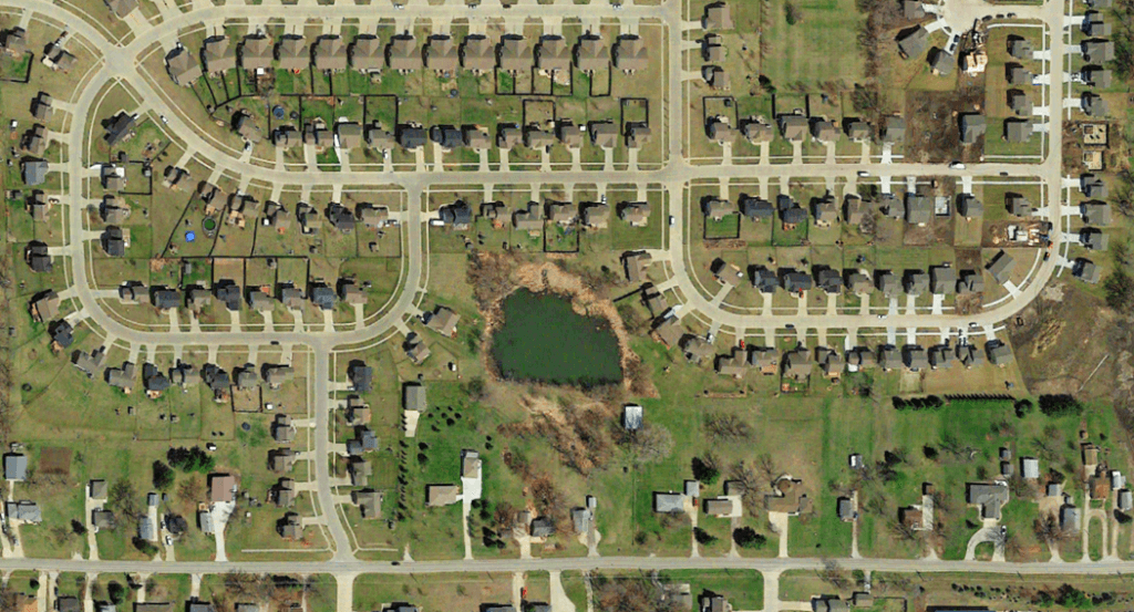 Satellite image of pond surrounded by residential neighborhoods