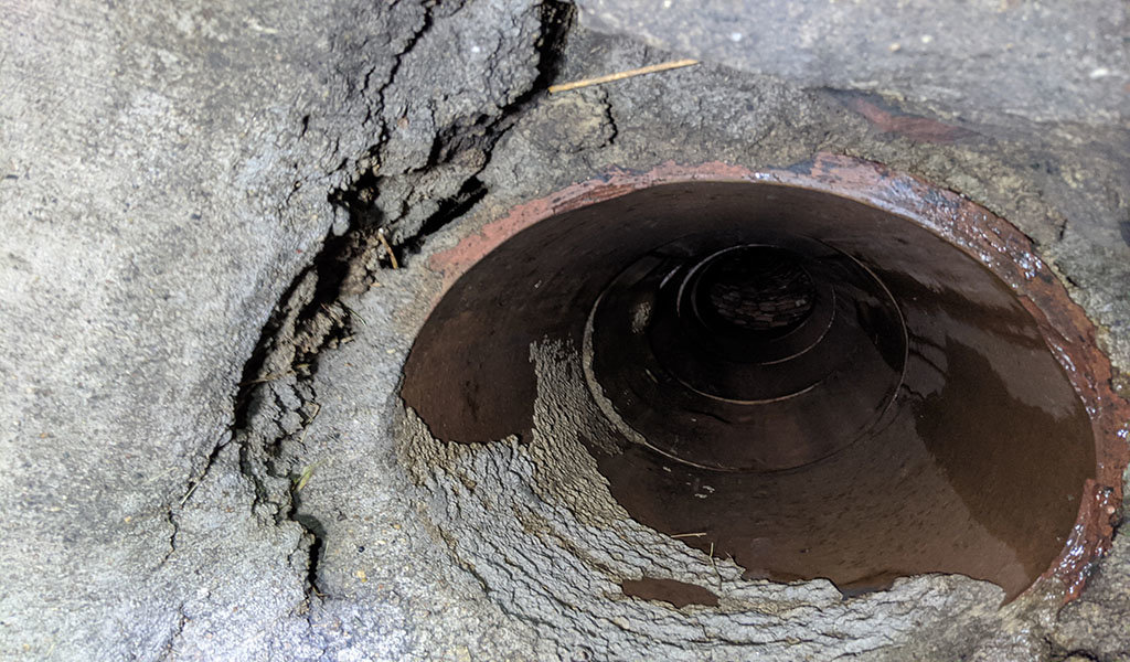 old pipe with cracked surrounding cement